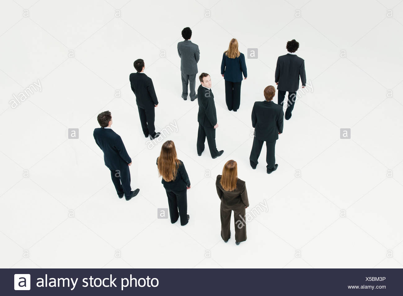Businessman standing in midst of other anonymously dressed professionals - Stock Image