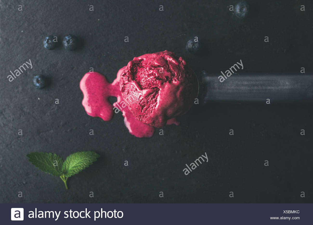 Melting scoop of blueberry ice-cream with mint leaves over black slate stone background, top view, selective focus, horizontal composition - Stock Image