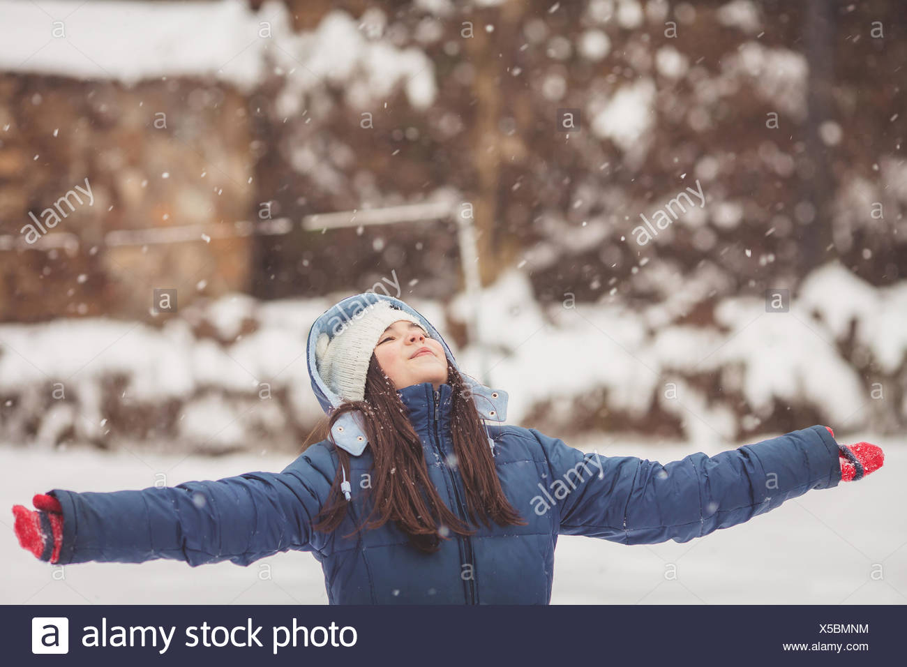 Girl standing in the snow looking up at the sky with outstretched arms - Stock Image