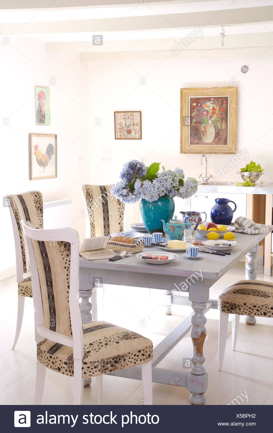 Upholstered White Painted Chairs At Painted Blue Table In French Country  Kitchen With Painted Wooden Flooring
