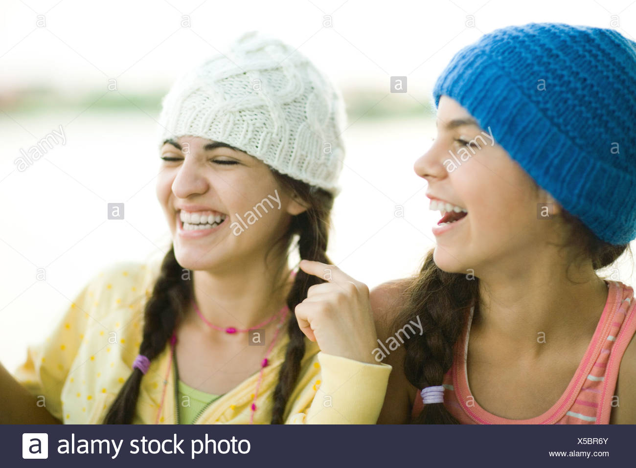 Young female friends wearing knit hats, laughing - Stock Image