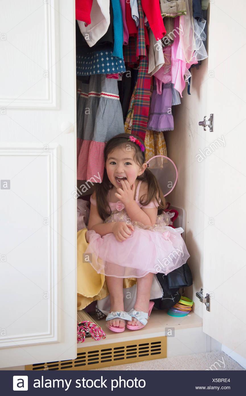 Girl in princess costume hiding in cupboard - Stock Image