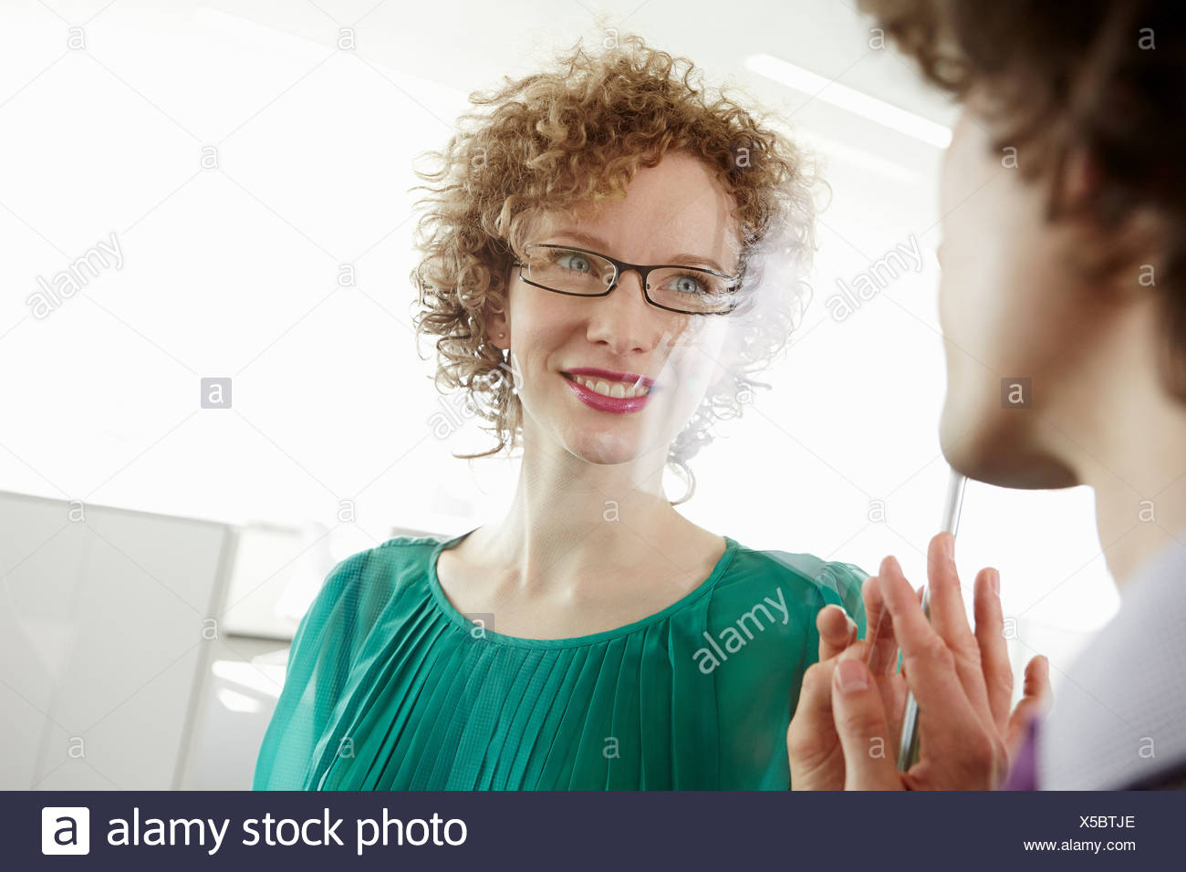 Businessman and woman holding hands against glass wall, separated - Stock Image