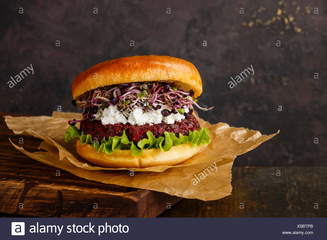 Beet burger with soft cheese and radish sprouts on dark background - Stock Image