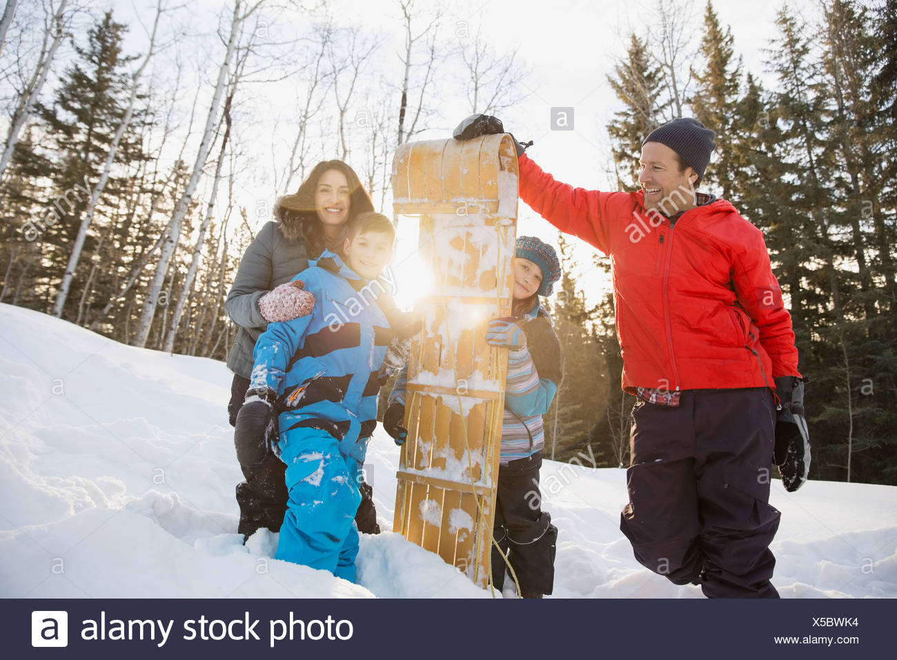 Portrait of smiling family and toboggan outdoors - Stock Image