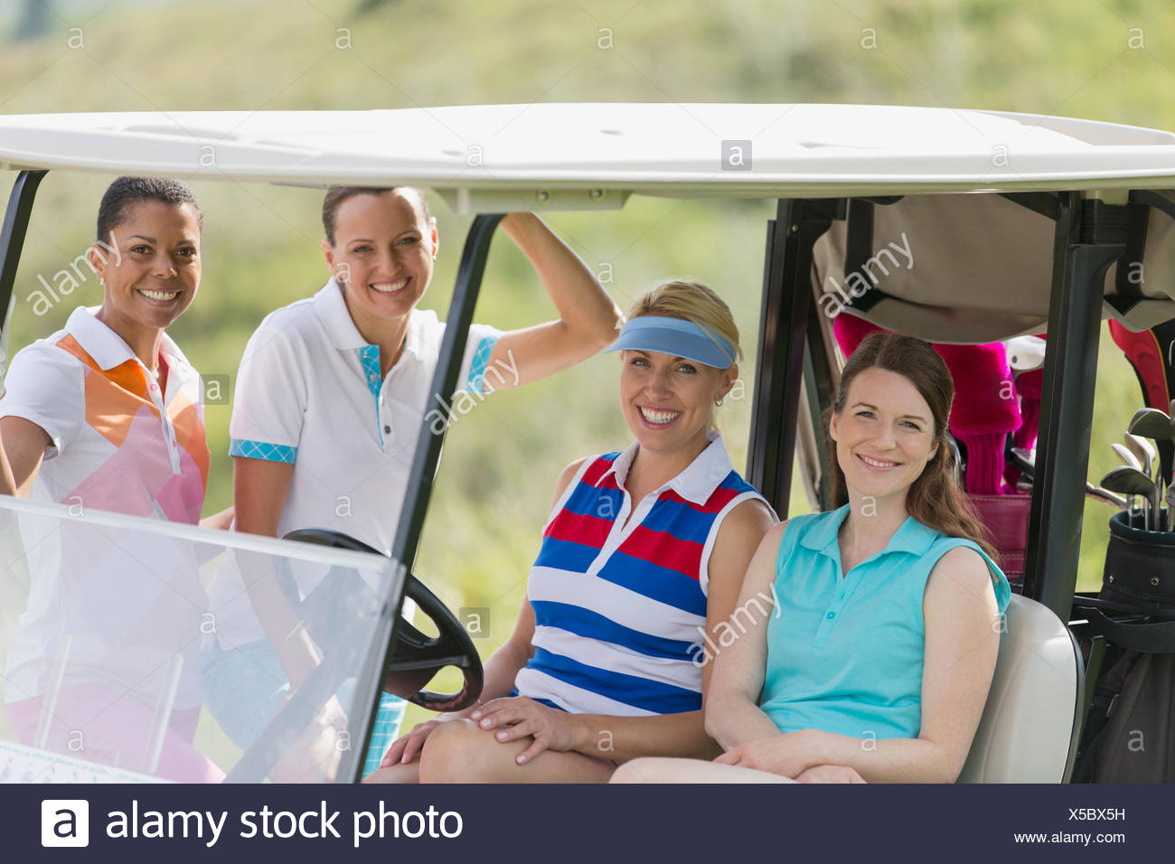 portrait of four female golfers by golf cart - Stock Image