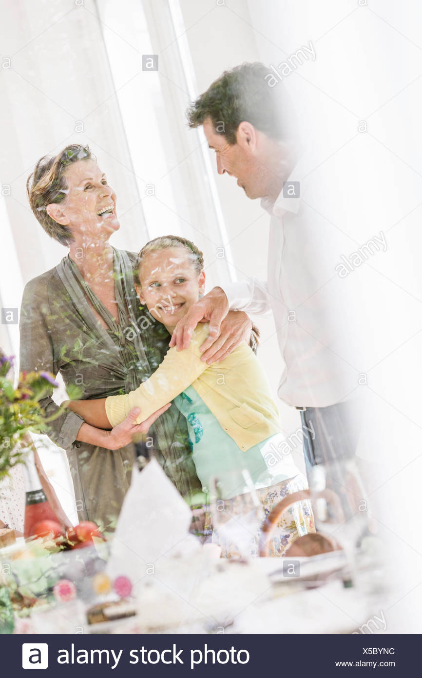 Looking through window at girl hugging grandmother in dining room - Stock Image