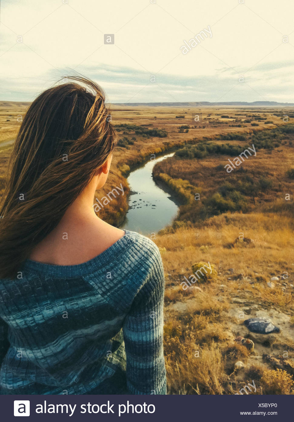 Canada, Saskatchewan, Val Marie, Rear view of woman overlooking prairie and river vista in fall Stock Photo