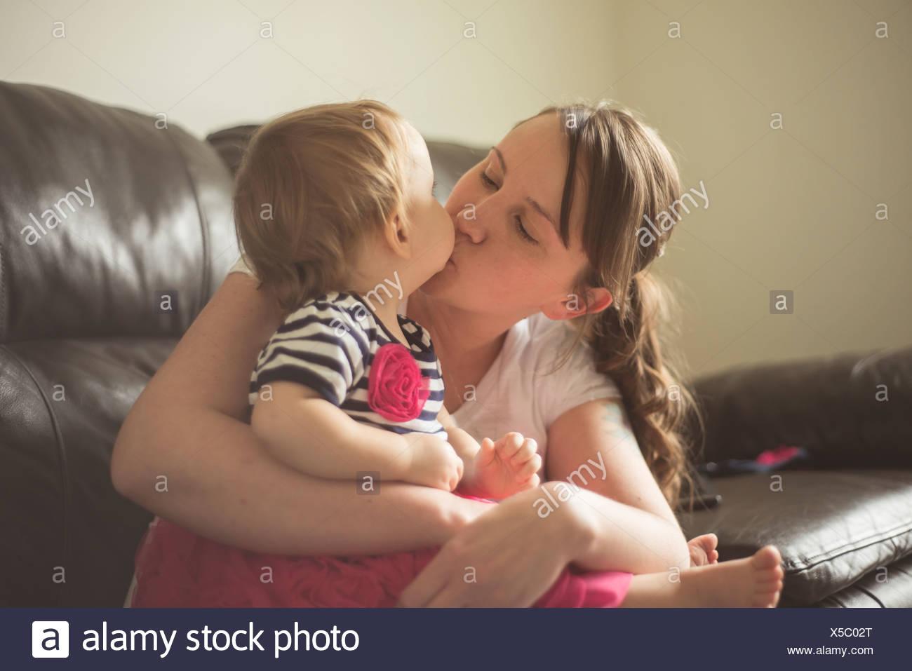 Female toddler sitting on mothers lap on sofa - Stock Image