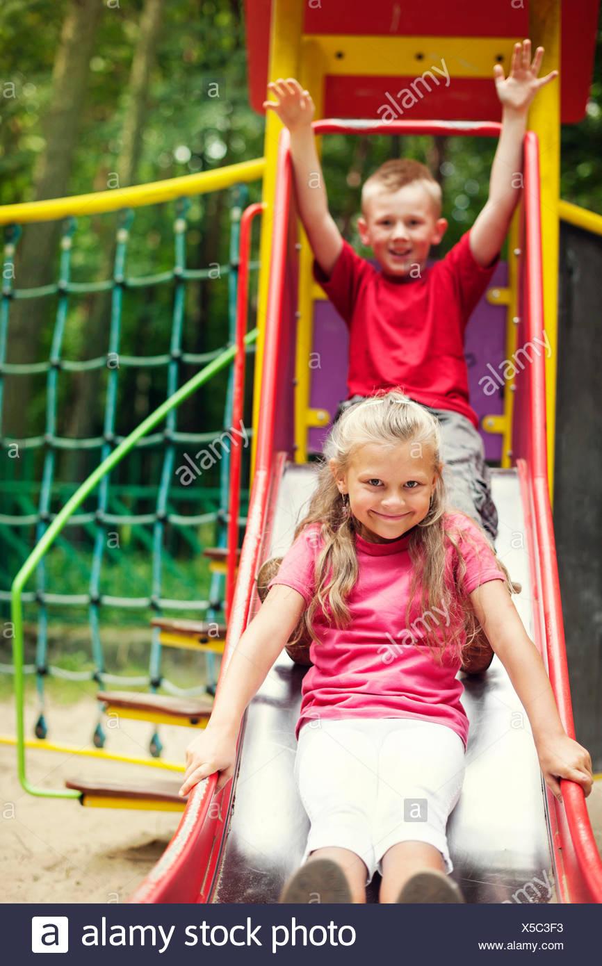 Two kids having fun on slide, Debica, Poland - Stock Image