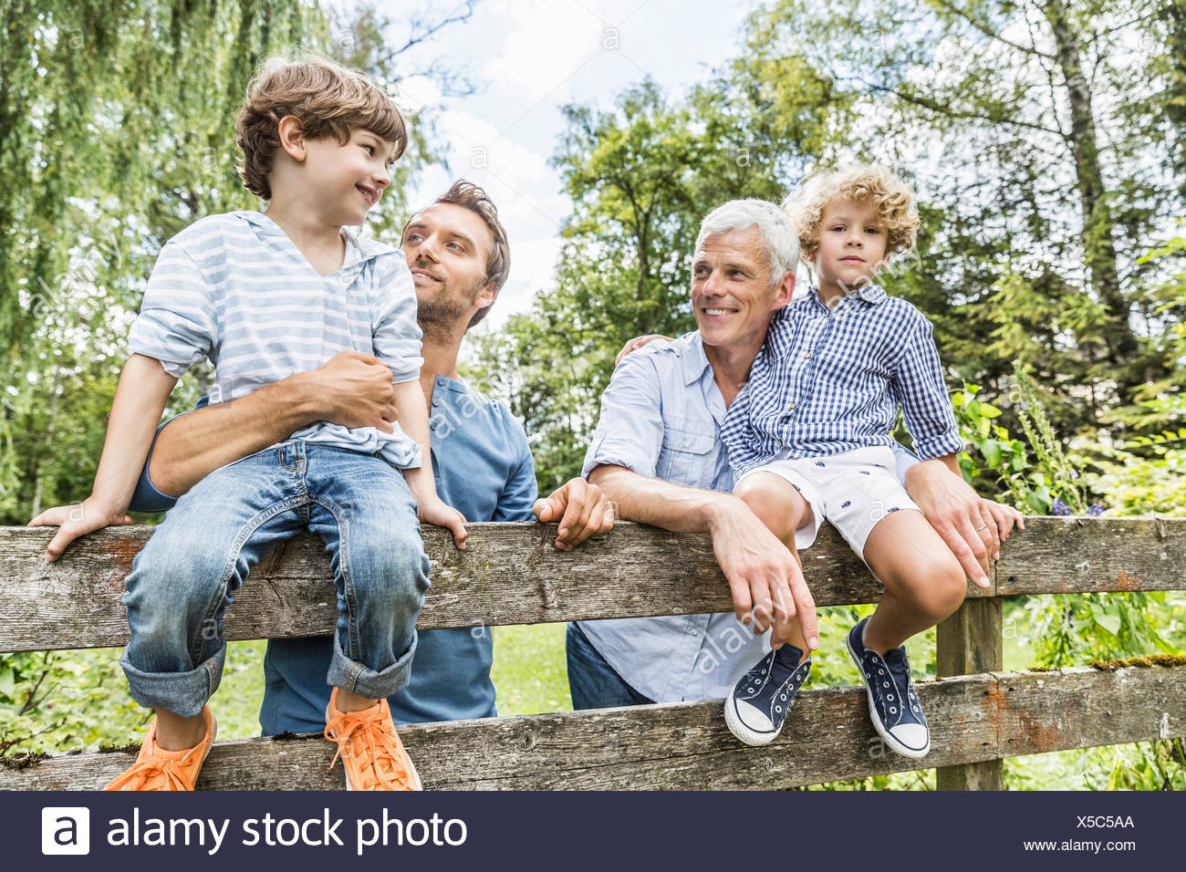 Portrait of two boys with father and grandfather sitting on fence  in garden - Stock Image
