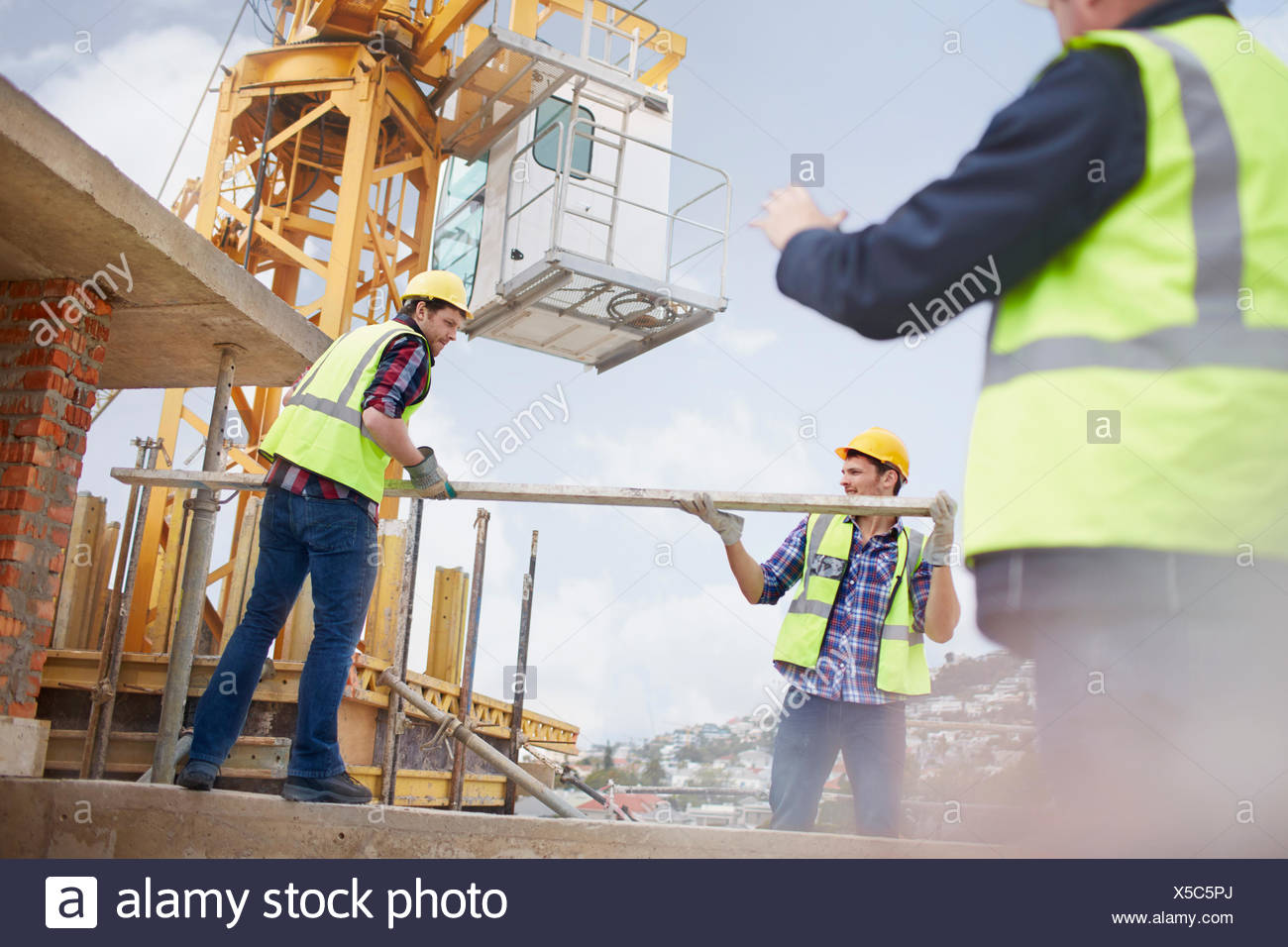 Construction workers lifting metal pole below crane at construction site Stock Photo
