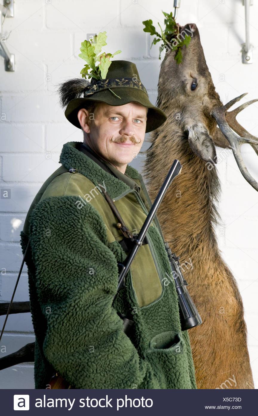Deer, cooling, hang, hunter, prey, shoots, hunting game, half portrait, animal, hygiene, hunt, red deer, venison, deadly, gun, man, occupation, hobby, at the side, people, hooks, oak leaves, pride, beard, moustache, care, - Stock Image