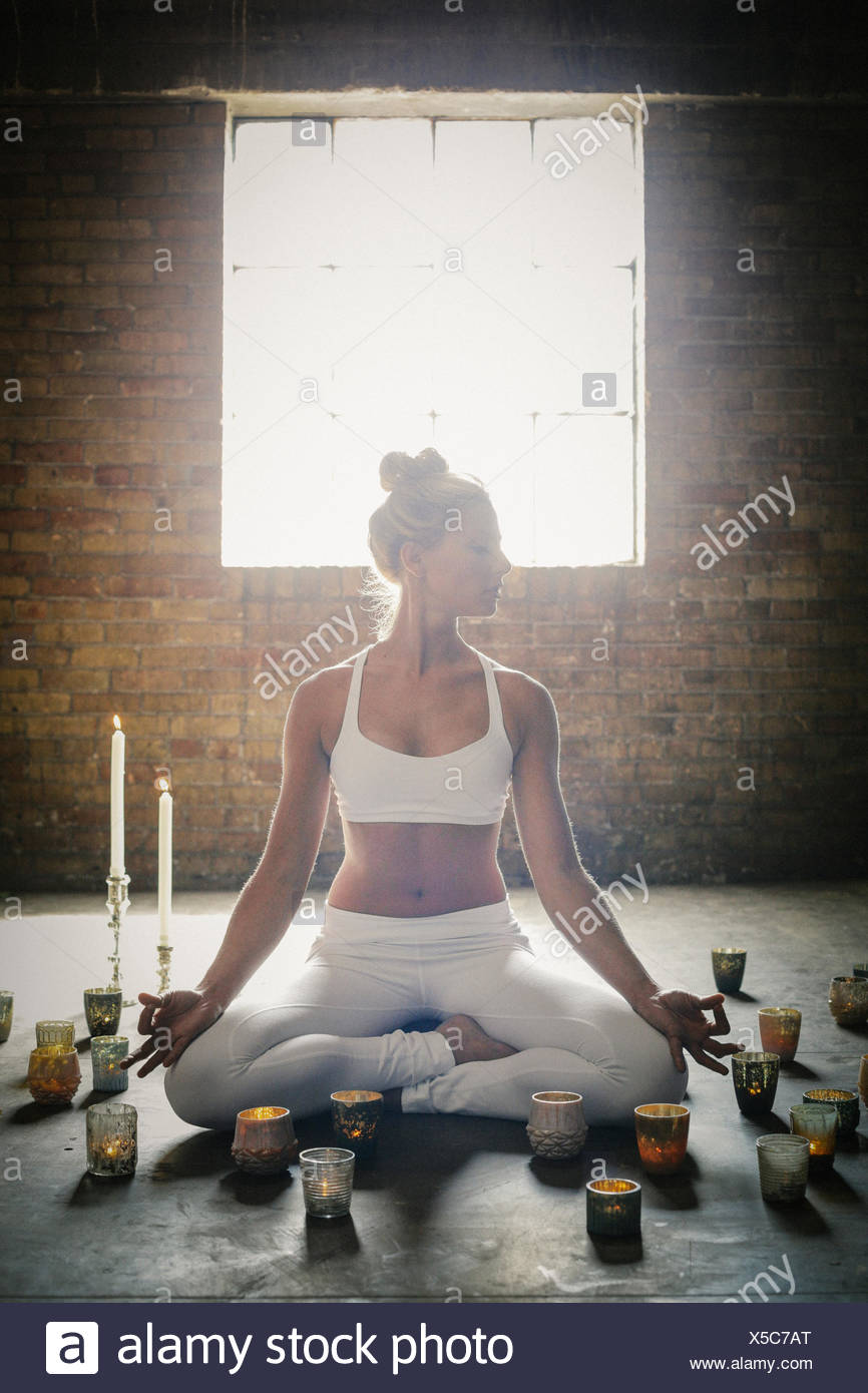 A blonde woman in a white crop top and leggings, sitting on the floor surrounded by candles, doing yoga. - Stock Image