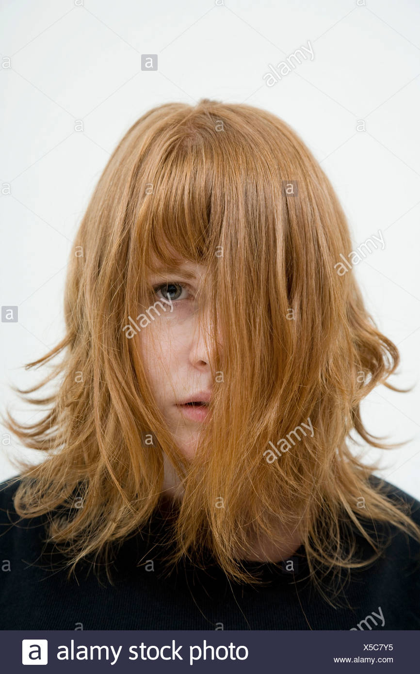 A woman with tousled hair hanging in her face - Stock Image