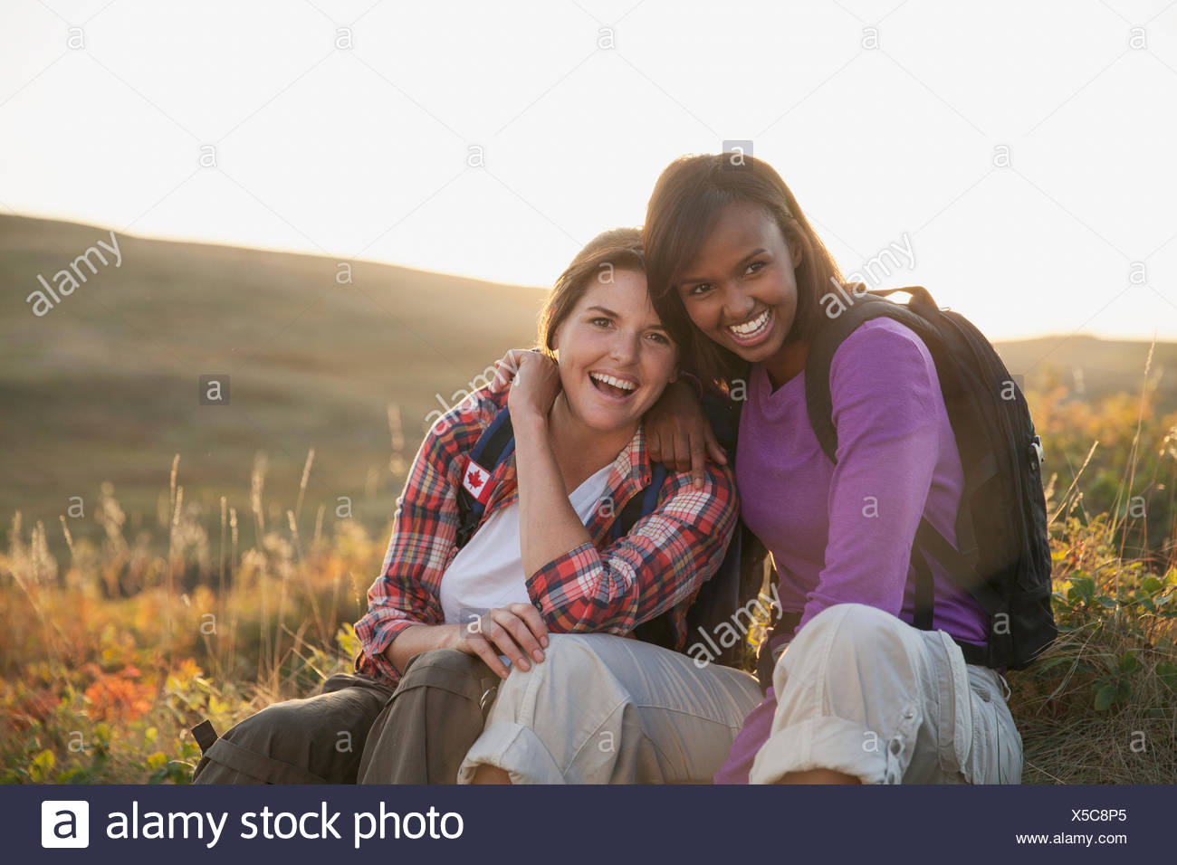 Girlfriends laughing together outdoors. - Stock Image