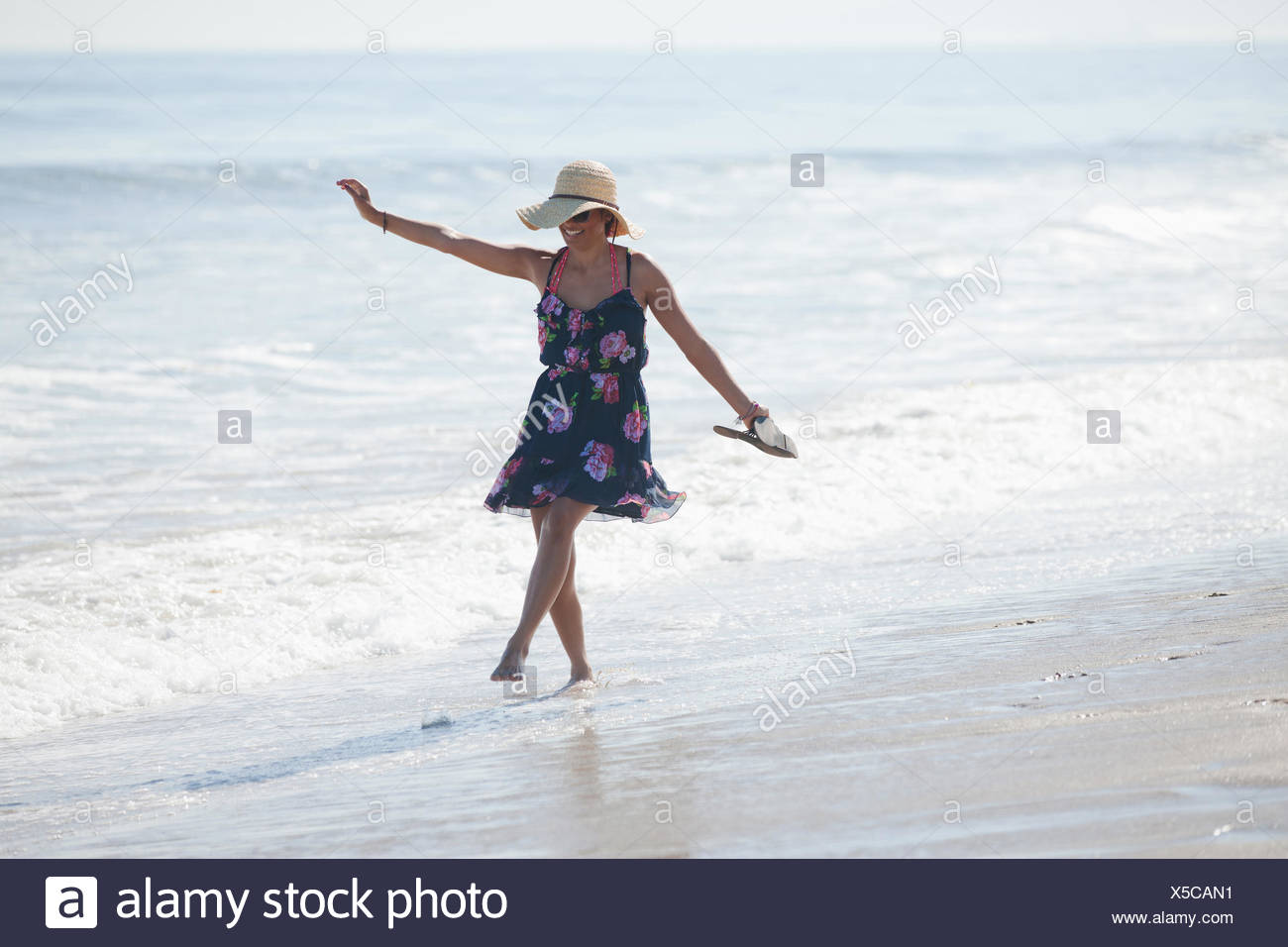 Woman carrying sandals on beach Stock Photo