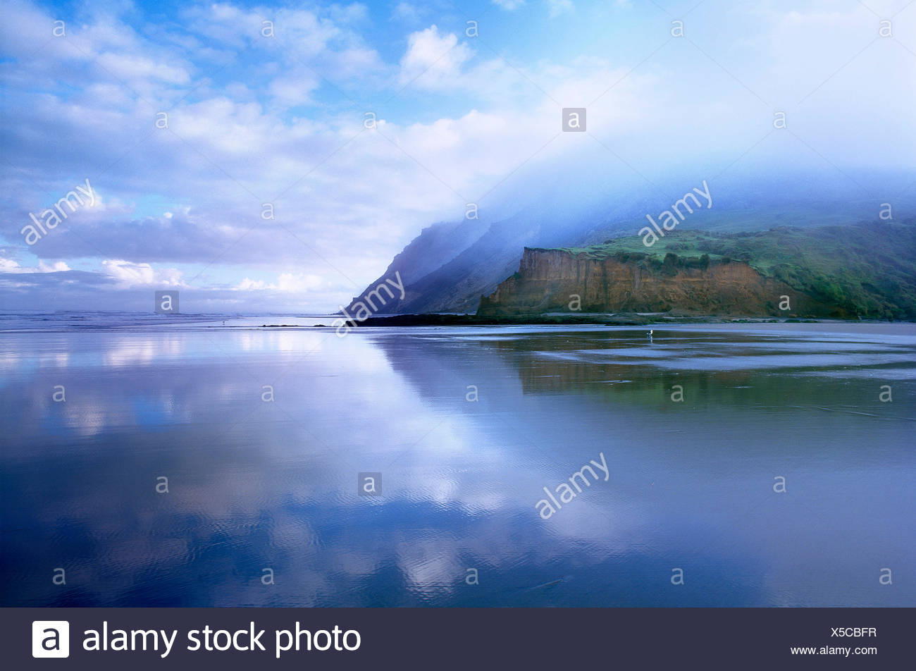 New Zealand. North Island. Low level cloud over west coast cliffs and beach. - Stock Image