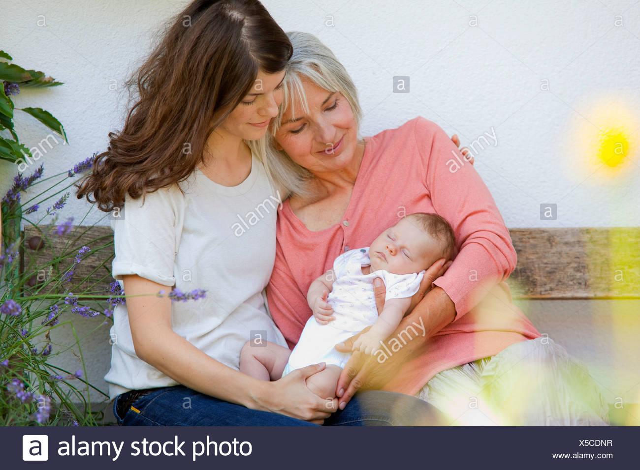 Germany, Bavaria, Three generations sitting together - Stock Image