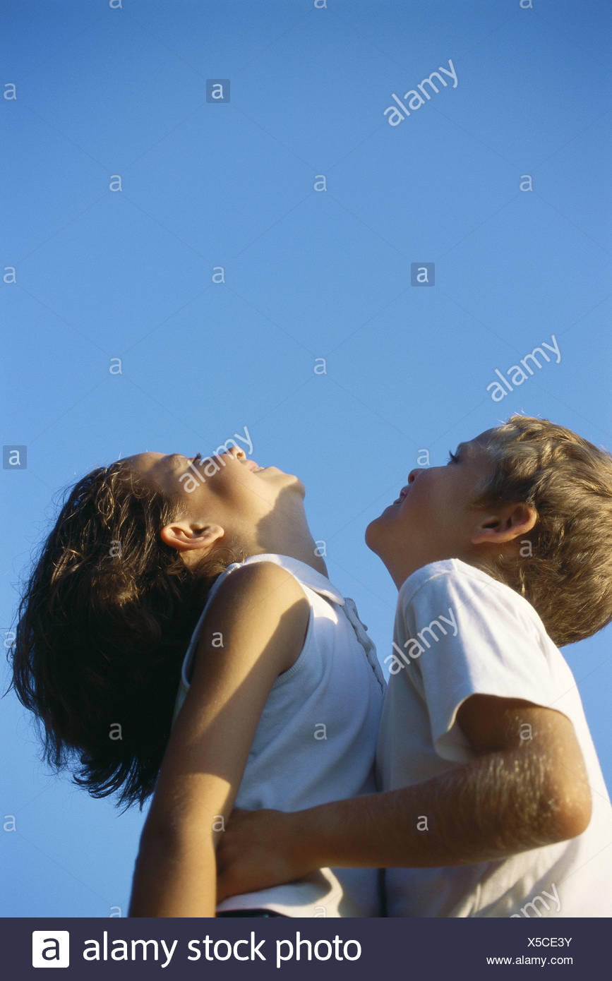 Two children standing close together, heads back - Stock Image