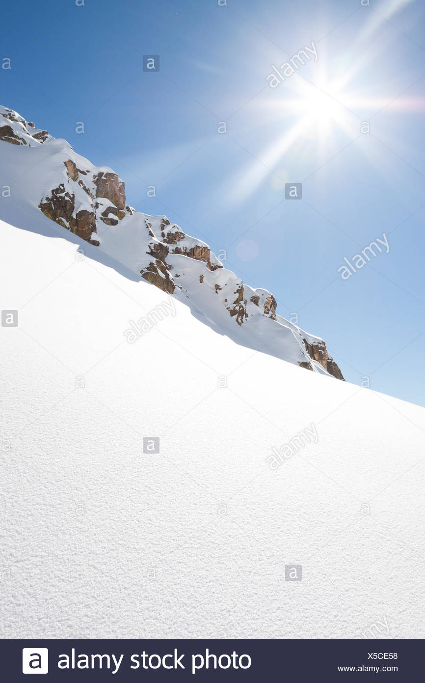The sun shines bright on a fresh slope in the Beehive Basin near Big Sky, Montana. - Stock Image