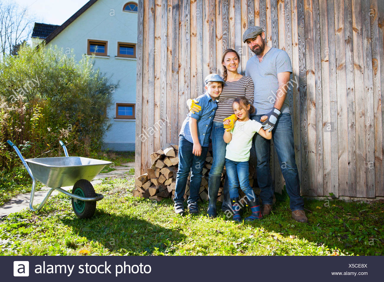 Family in garden with wheelbarrow, Munich, Bavaria, Germany - Stock Image