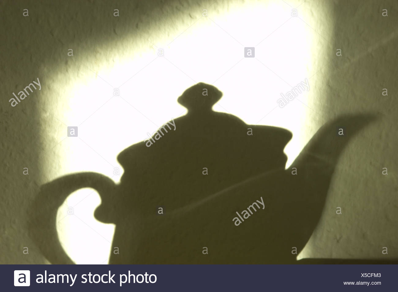 The morning sun is drawing the shaddow of a coffepot on the wall - Stock Image