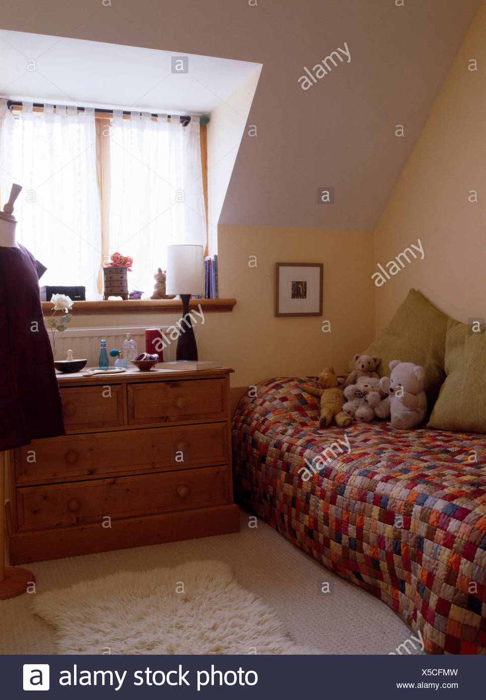 Patchwork quilt on single bed in child's attic bedroom with pine chest of drawers - Stock Image