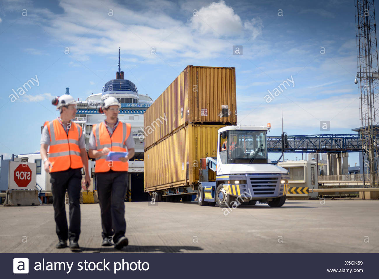 Port workers and truck unloading shipping containers from ship to port - Stock Image