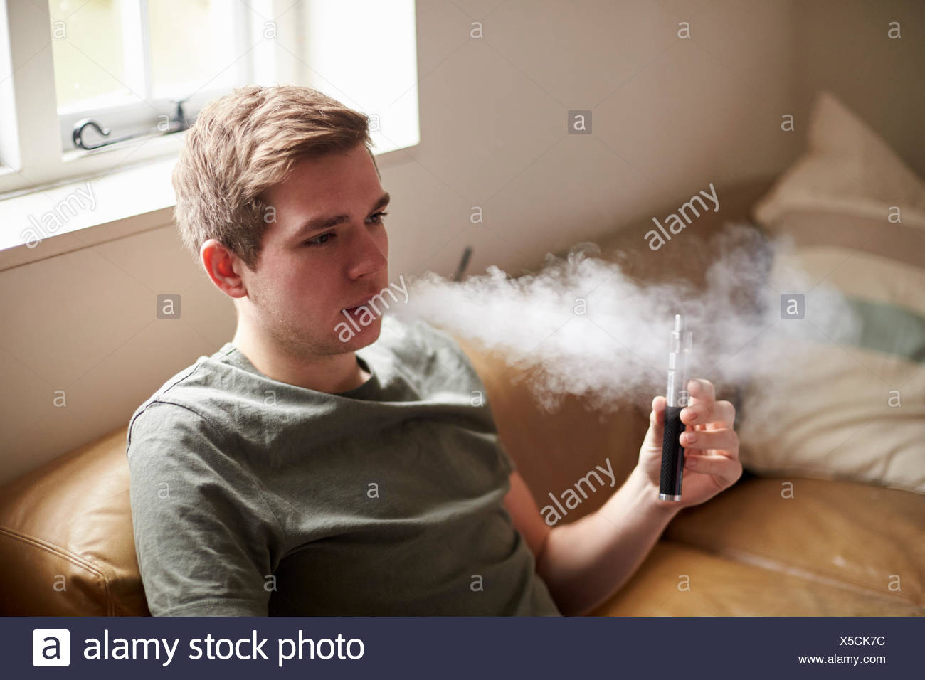 Young Man Using Vapourizer As Smoking Alternative - Stock Image