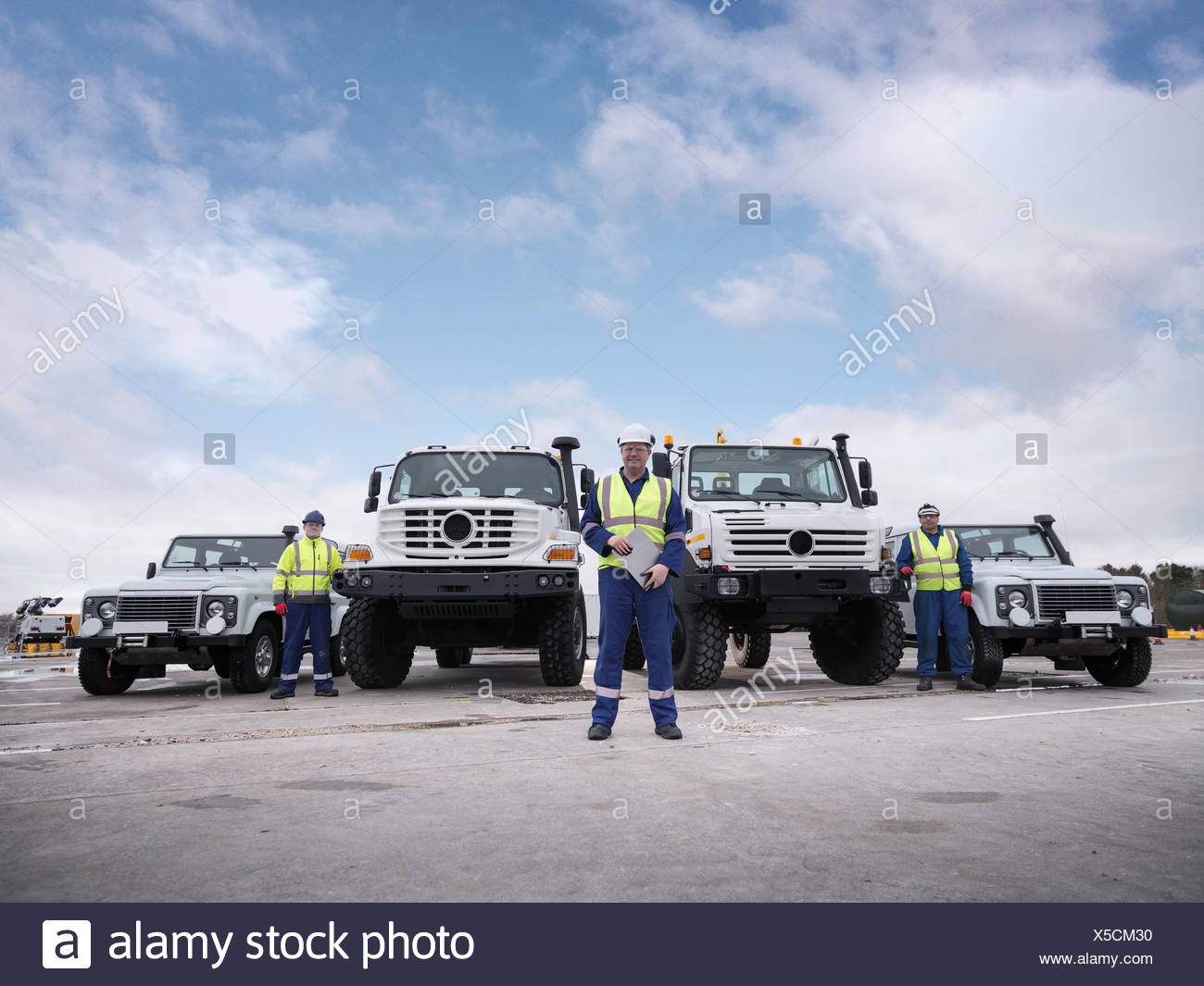 Portrait of Emergency Response Team workers with specialist trucks - Stock Image