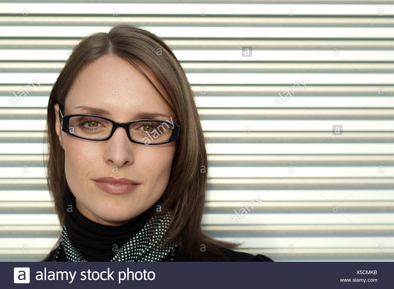 Portrait of a woman against shutters - Stock Image