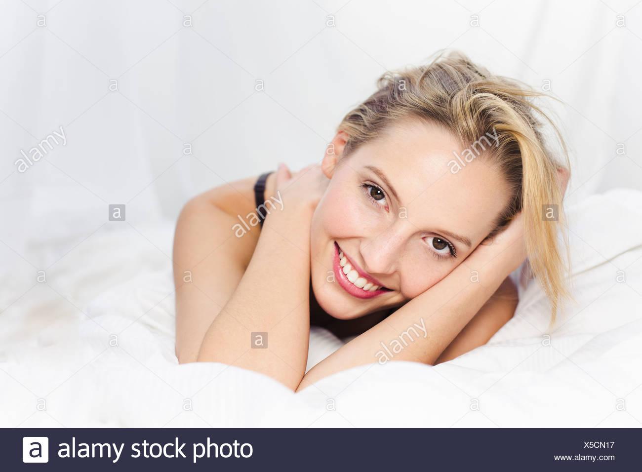 Young woman looking at camera, smiling - Stock Image