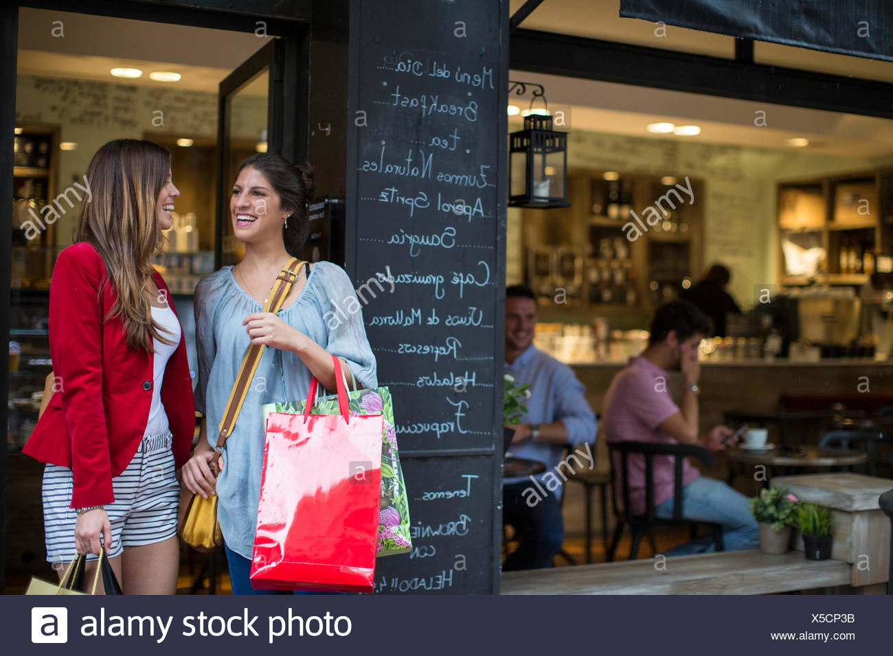 Two young female friends outside cafe carrying shopping bags - Stock Image