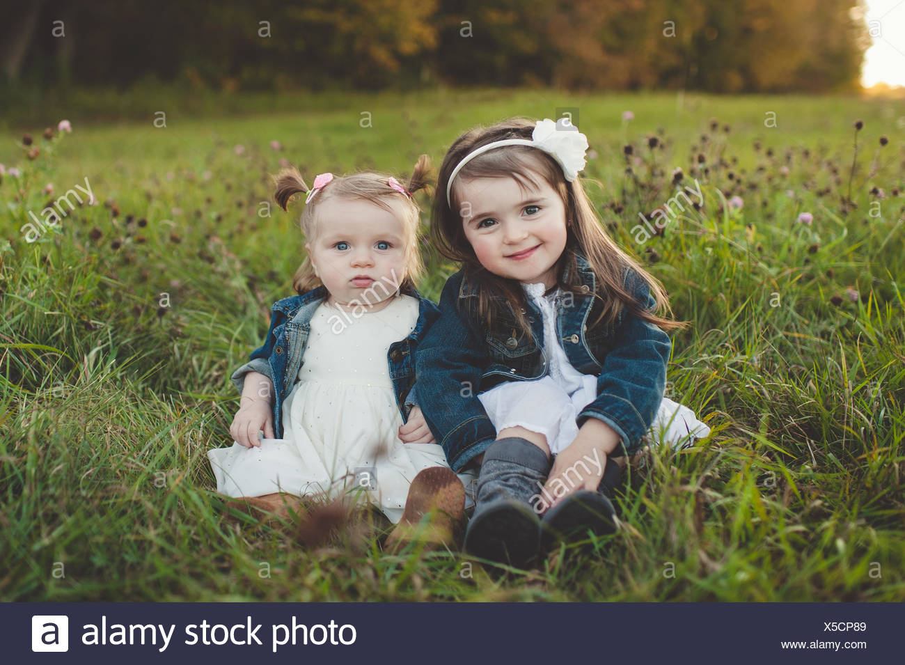 Portrait of young girl and baby sister in field - Stock Image