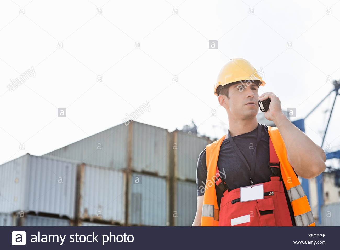 Male worker using walkie-talkie in shipping yard - Stock Image