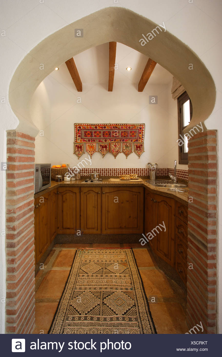 View Through Moroccan Style Arch To Small Spanish Kitchen With Wooden Units And Oriental Rug On Tiled Floor Stock Photo Alamy