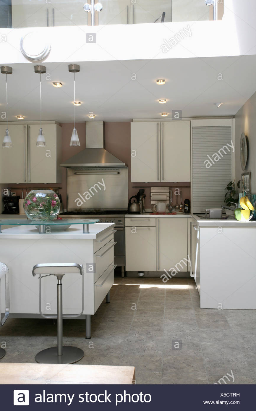 Recessed lighting in modern white kitchen with grey granite flooring and rectangular island unit - Stock Image