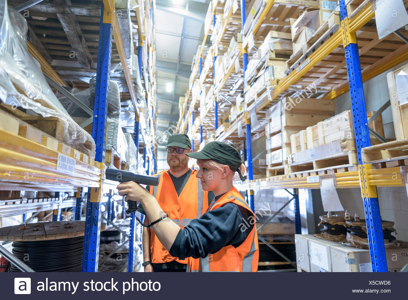 Storage workers scanning parts in train works warehouse - Stock Image