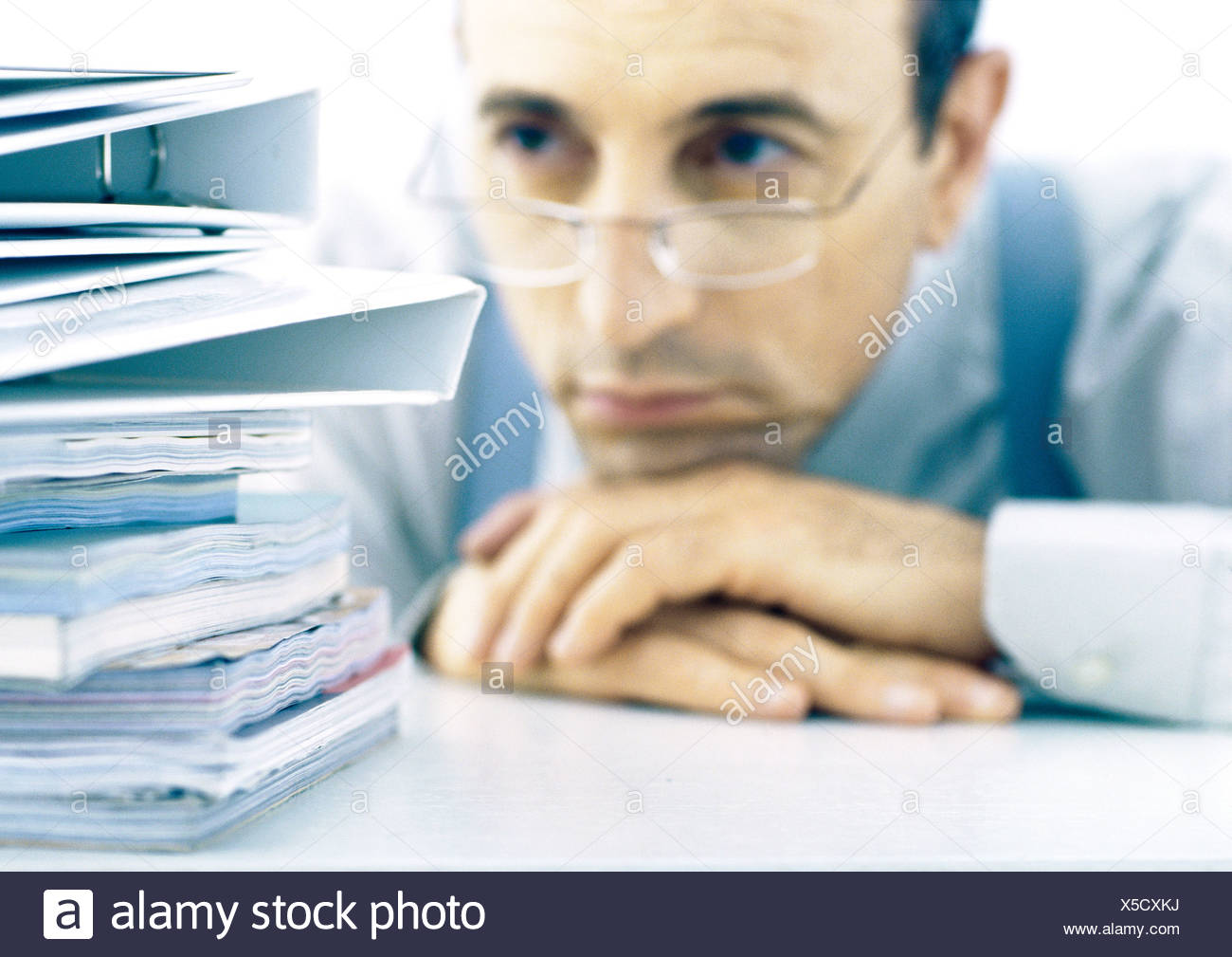 Man resting head on hands, looking at stack of files - Stock Image