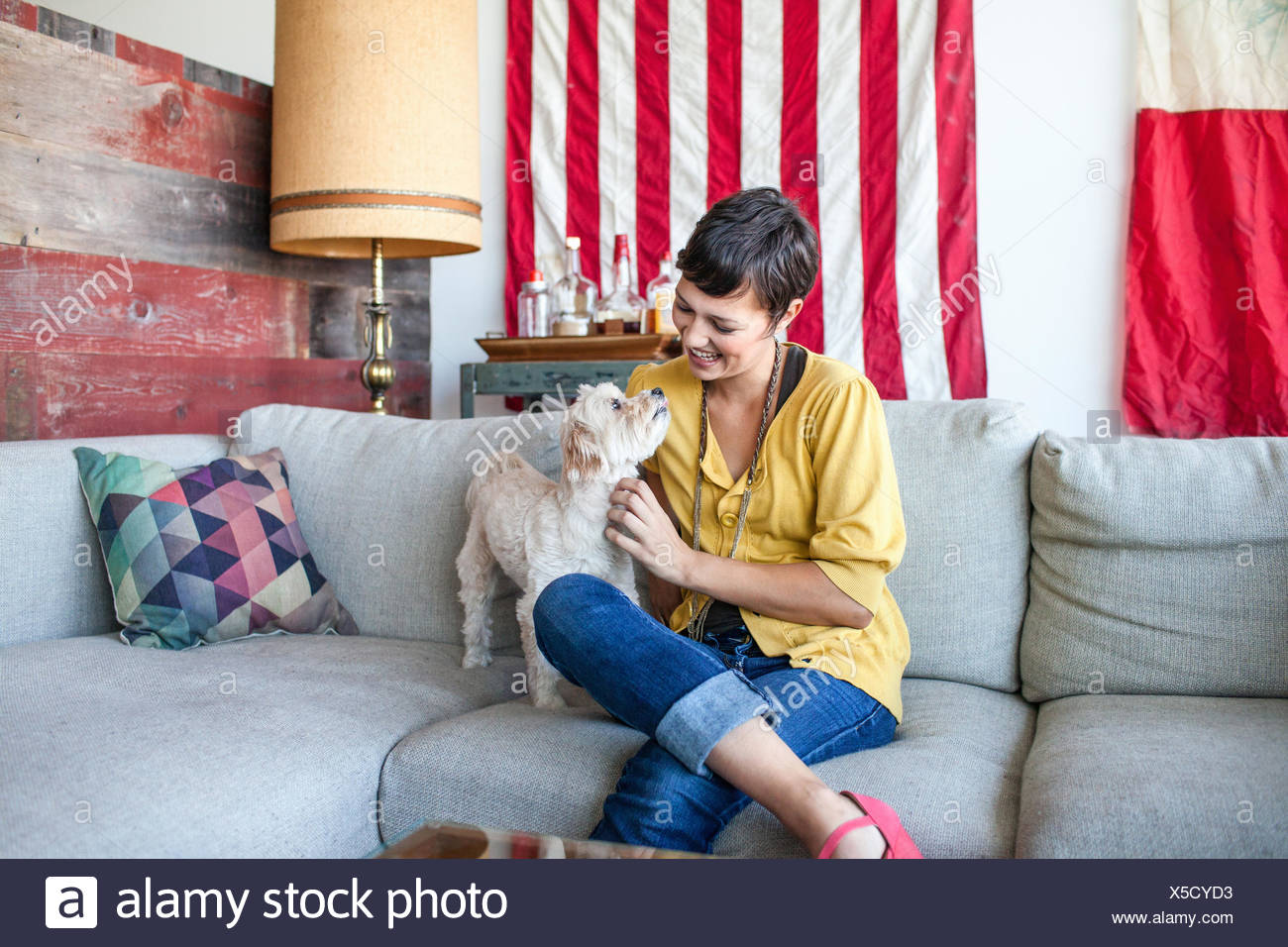 Young woman petting dog on living room sofa - Stock Image