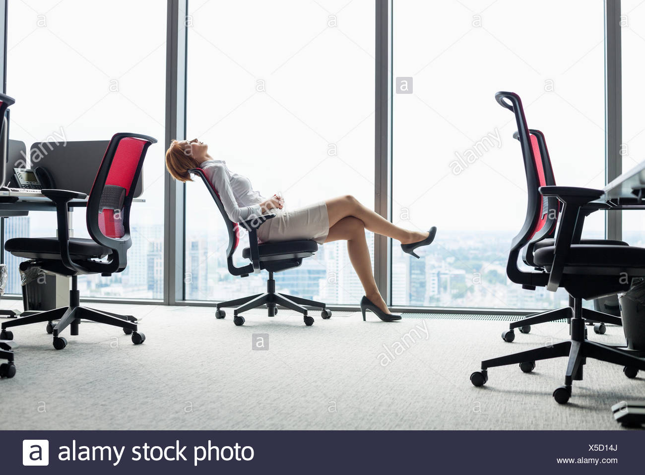 Full length side view of young businesswoman leaning back in chair at office - Stock Image