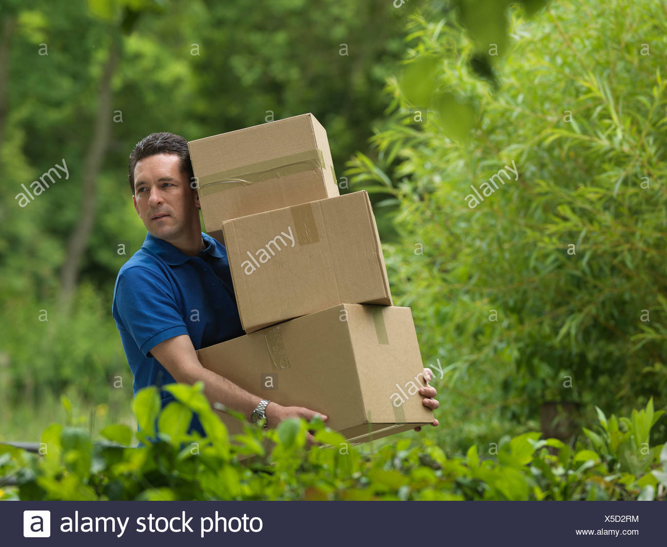 man carrying boxes - Stock Image