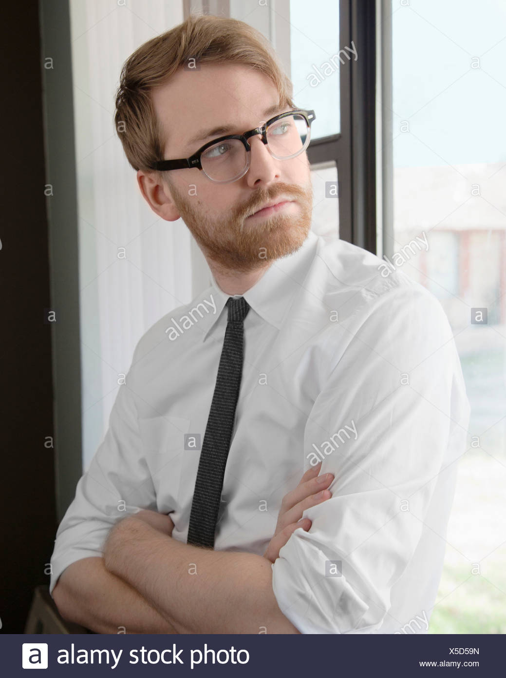 Young man wearing spectacles and tie looking away - Stock Image