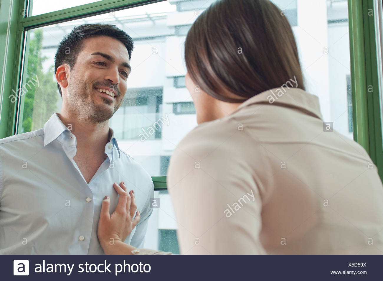 Young colleagues flirting in office - Stock Image
