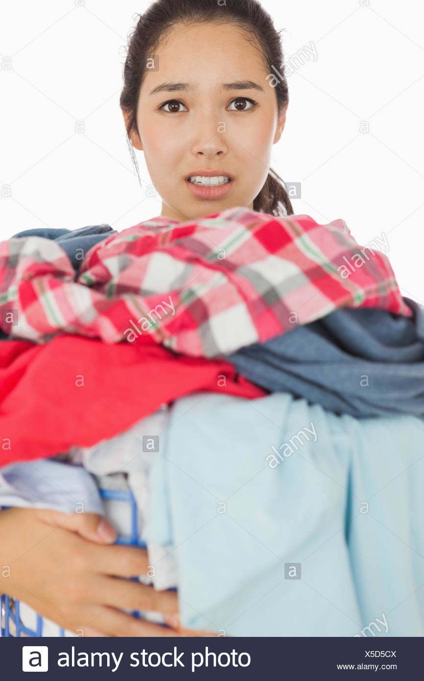 Woman overwhelmed with amount of dirty laundry - Stock Image