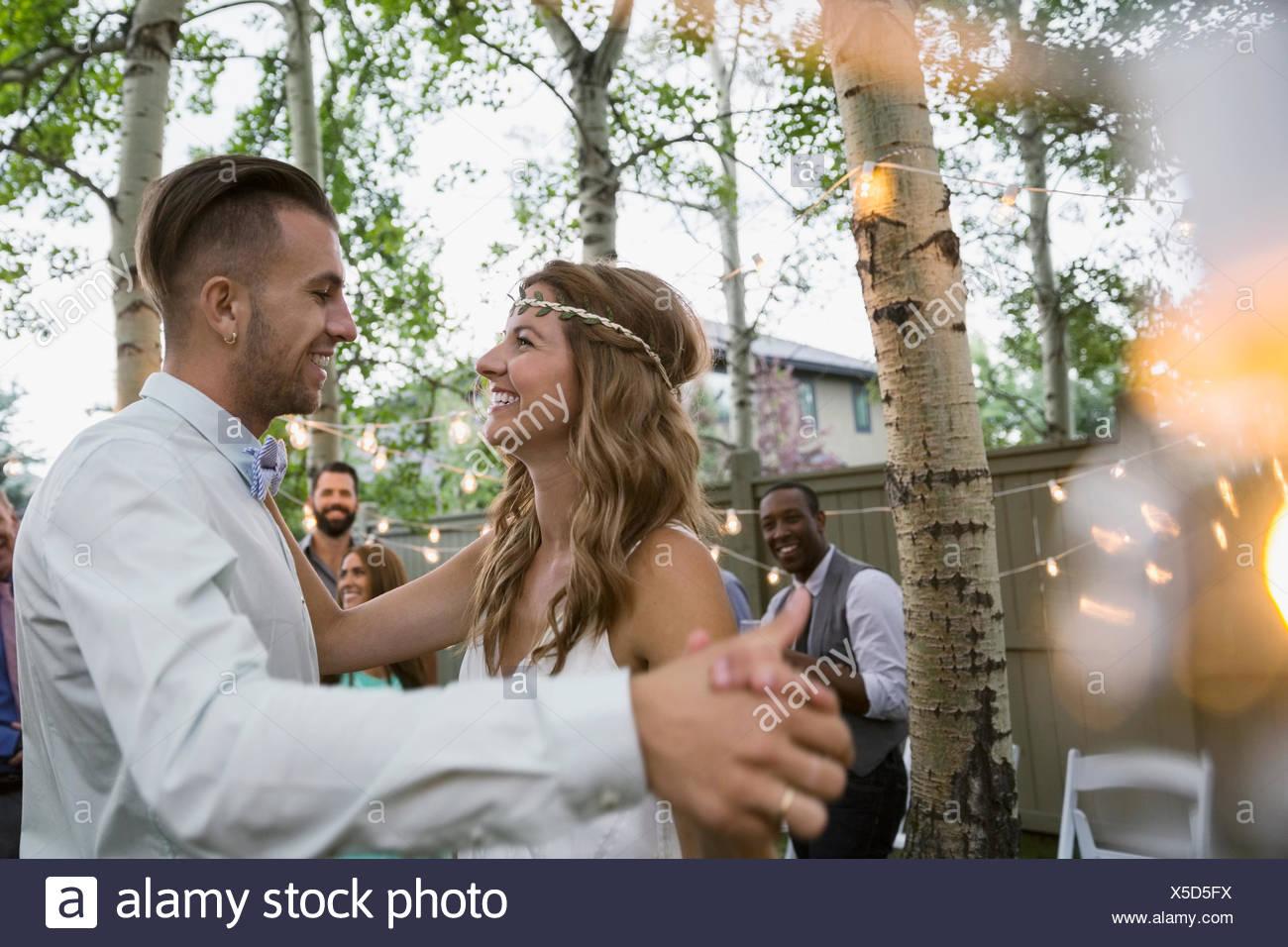 Bride and groom dancing at backyard wedding reception - Stock Image