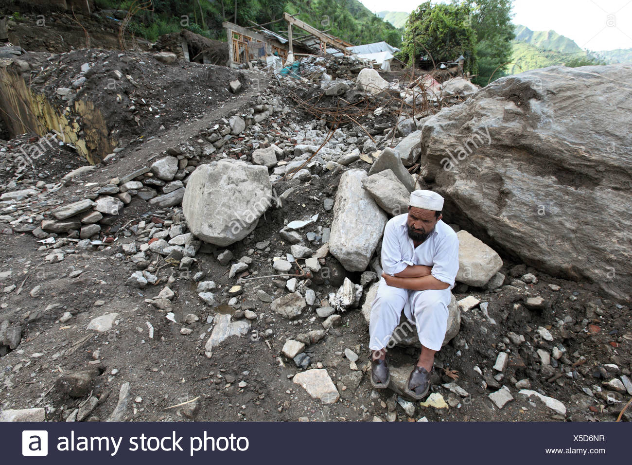 A man in front of the ruins of his house after the flood disaster, Kokarai, Pakistan - Stock Image