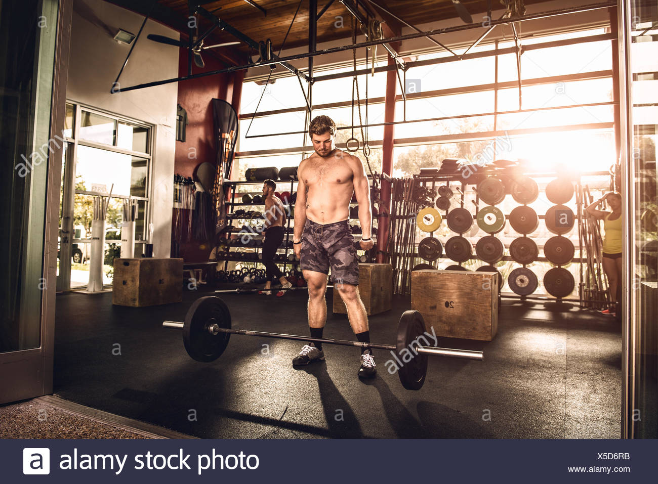 Bodybuilder looking down at barbell in gym - Stock Image