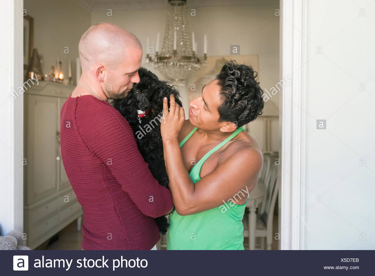 Norway, Couple holding black dog (canis lupus familiaris) - Stock Image